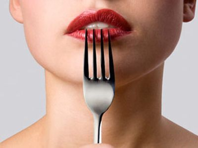 moteris with red lipstick pressing a fork to her lips